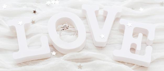 Word love sur un tissu blanc avec une bague de fiançailles en diamant. bon pour les cartes de saint valentin. Photo Premium