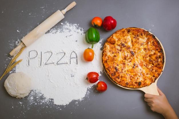Word pizza écrit sur de la farine avec une pizza savoureuse Photo gratuit