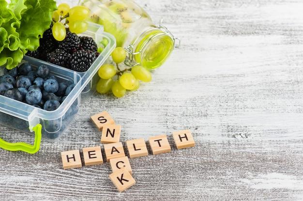 Word snack et baies dans une boîte à lunch Photo Premium