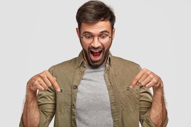 Wow, C'est Incroyable! Un Jeune Homme Surpris, Choqué, Regarde Avec Surprise Vers Le Bas, Pointe Avec Les Deux Index, Habillé Avec Désinvolture, Ouvre Largement La Bouche D'étonnement, Isolé Sur Un Mur Blanc Photo gratuit