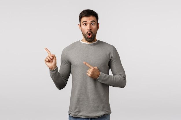 Wow Surprise Incroyable, Regardez ça. Bel Homme Barbu étonné Et étonné En Pull Gris, Haletant, étonné, Regardant Le Coin Supérieur Gauche, Indiquer La Promo, Photo Premium