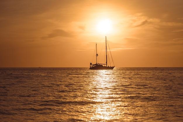 Yacht dans la mer tropicale au coucher du soleil Photo Premium