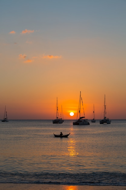 Yacht à la mer au coucher du soleil Photo gratuit