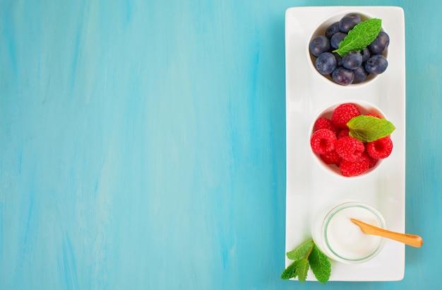 Yaourt aux bleuets et framboises - concept santé et régime alimentaire. petit-déjeuner équilibré Photo Premium