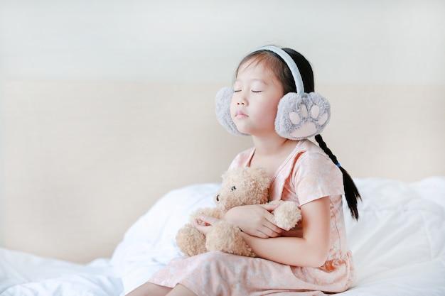 Yeux fermés petite fille portant des cache-oreilles d'hiver et embrassant un ours en peluche assis sur le lit à la maison. Photo Premium