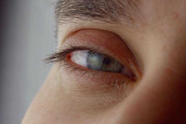 Les yeux rétrécis des hommes. regard fatigué direct dans le gros plan du cadre. Photo Premium