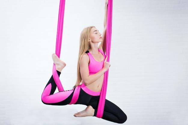 Yoga Anti-gravité Belle Jeune Fille Sur Un Hamac En Soie Rose. Médite Photo Premium