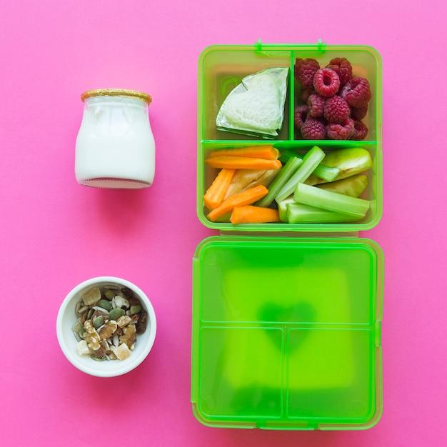 Yogourt et muesli près de la boîte à lunch avec de la nourriture saine Photo gratuit