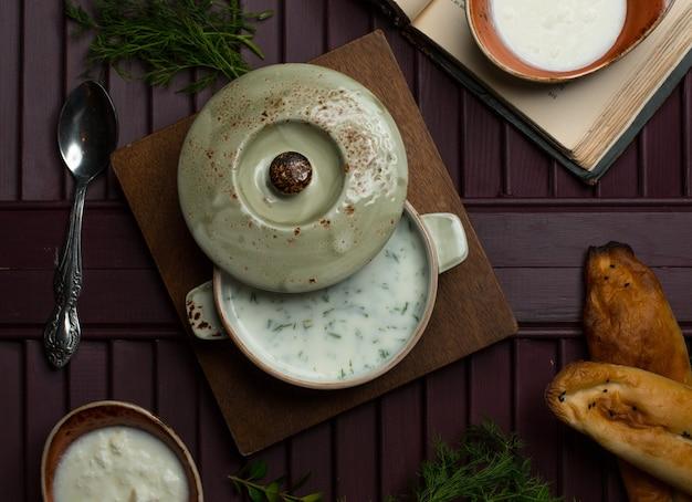 Yogourt soupp avec des légumes dans une casserole sur une planche de bois. Photo gratuit