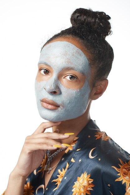 Yong drôle avec masque de beauté d'argile sur le modèle isolé de la peau Photo Premium