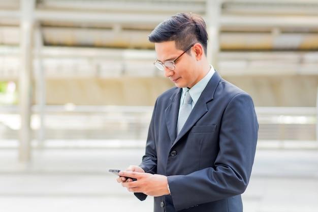 Young asia bel homme d'affaires avec son smartphone debout sur le trottoir de la ville moderne. Photo Premium