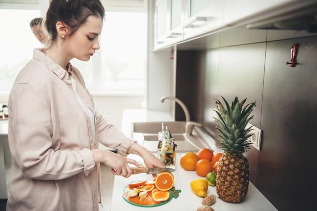 Young Caucasian Couple Préparer Une Salade De Fruits Ensemble Dans La Cuisine Trancher Les Fruits Photo Premium