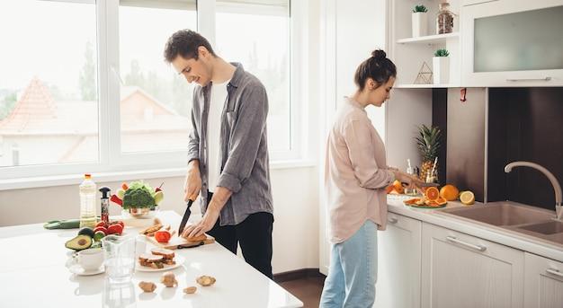 Young Caucasian Couple Trancher Les Fruits Dans La Cuisine Et Préparer Le Petit Déjeuner Ensemble Photo Premium