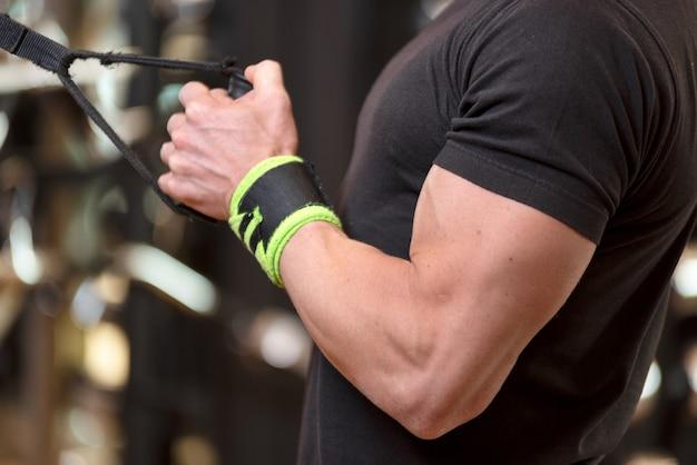 Young fit homme musclé se bouchent faire des triceps abaisser exercice de corde extension dans un centre de remise en forme moderne. Photo Premium