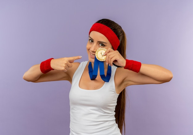 Young Fitness Woman In Sportswear Avec Bandeau Avec Médaille D'or Autour De Son Cou Montrant Et Pointant Avec Le Doigt Sur Elle Souriant Debout Sur Mur Gris Photo gratuit