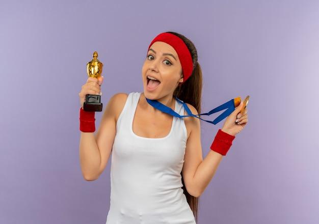 Young Fitness Woman In Sportswear Avec Bandeau Avec Médaille D'or Autour De Son Cou Tenant Son Trophée En Criant Heureux Et Excité Debout Sur Un Mur Gris Photo gratuit