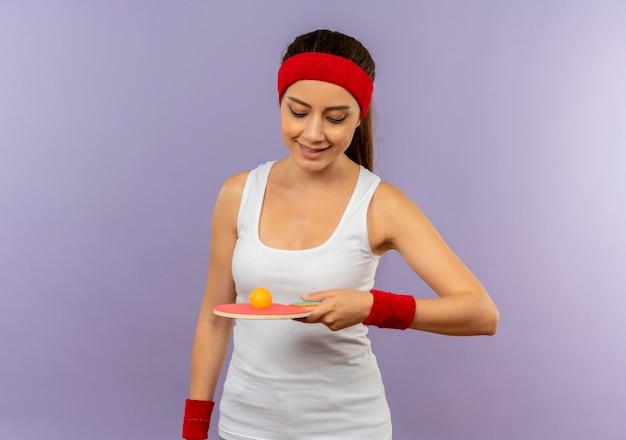 Young Fitness Woman In Sportswear Avec Bandeau Tenant La Raquette Et La Balle Pour Le Tennis De Table En Le Regardant Avec Le Sourire Sur Le Visage Debout Sur Un Mur Gris Photo gratuit