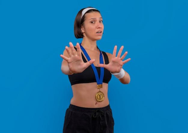 Young Fitness Woman In Sportswear Avec Médaille D'or Autour De Son Cou Faisant Le Geste De Défense Avec Les Mains Peur Debout Sur Le Mur Bleu Photo gratuit