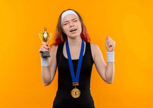 Young Fitness Woman In Sportswear Avec Médaille D'or Autour De Son Cou Levant Les Poings Tenant Le Trophée Avec Une Expression Agacée Debout Sur Un Mur Orange Photo gratuit