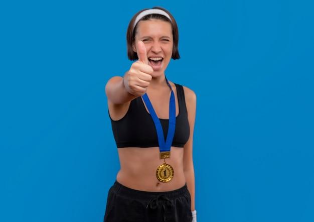 Young Fitness Woman In Sportswear Avec Médaille D'or Autour De Son Cou Montrant Les Pouces Vers Le Haut Se Réjouissant De Son Succès Heureux Et Excité Debout Sur Le Mur Bleu Photo gratuit