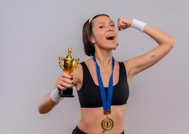 Young Fitness Woman In Sportswear Avec Médaille D'or Autour De Son Cou Tenant Son Trophée Levant Le Poing Heureux Et Excité Se Réjouissant De Son Succès Debout Sur Un Mur Blanc Photo gratuit