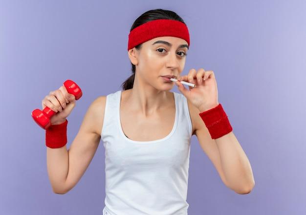 Young Fitness Woman In Sportswear Tenant Haltère Avec Cigarette Va Fumer Debout Sur Le Mur Violet Photo gratuit