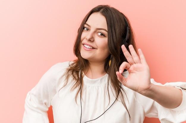 Young, plus la femme tout en courbes de taille écoute de la musique avec un casque gai et confiant, montrant le geste correct. Photo Premium