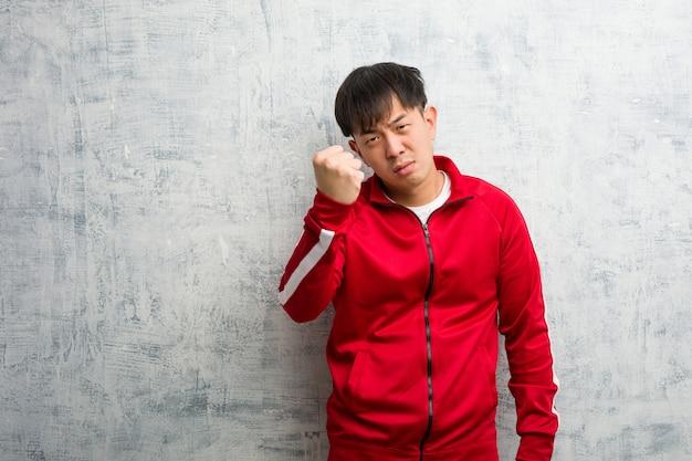 Young sport fitness chinois montrant le poing à l'avant, expression en colère Photo Premium