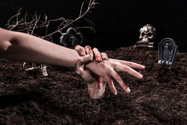 Zombie hand catching person au cimetière d'halloween Photo gratuit