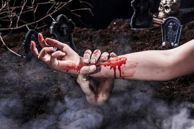 Zombie main tenant le bras de femme sanglante au cimetière d'halloween Photo gratuit