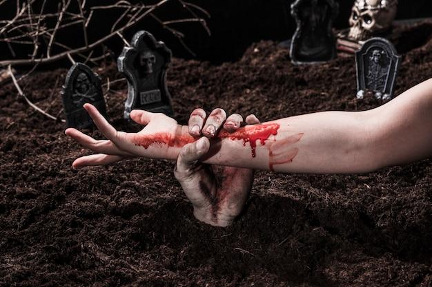 Zombie tenant une main féminine sanglante au cimetière d'halloween Photo gratuit
