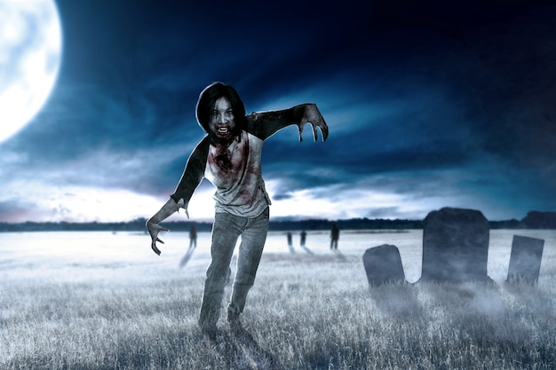 Zombies effrayants avec du sang et une plaie sur son corps se promener sur le terrain d'herbe Photo Premium