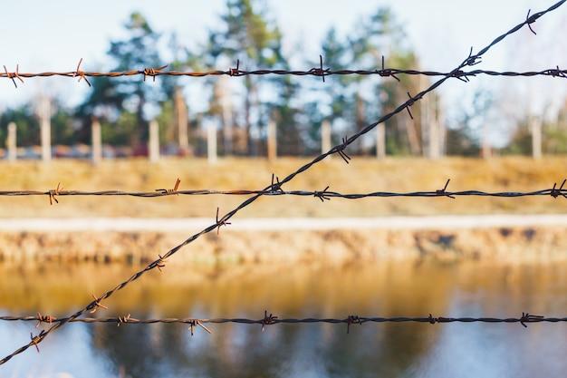 Zone dangereuse clôturée avec une clôture de barbelés Photo Premium