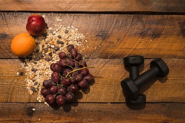 Alimentation saine avec des haltères sur fond en bois Photo gratuit