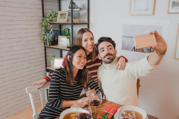 Amis prenant selfie au dîner de Noël Photo gratuit