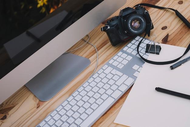 Appareil photo et feuille de papier près de l'ordinateur Photo gratuit
