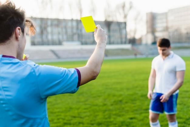 Arbitre méconnaissable montrant un carton jaune Photo gratuit