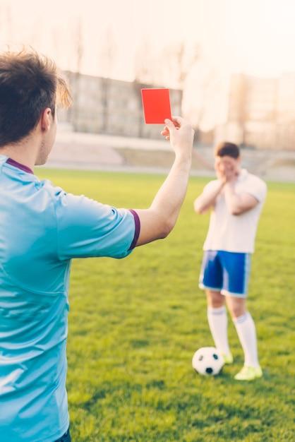 Arbitre sans visage montrant le carton rouge à l'athlète Photo gratuit