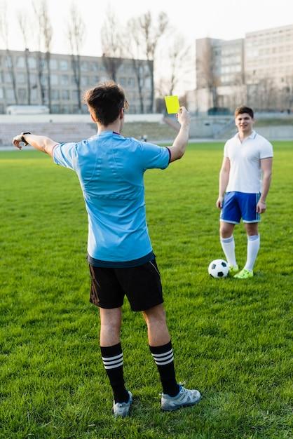 Arbitre sans visage montrant un carton jaune au sportif Photo gratuit
