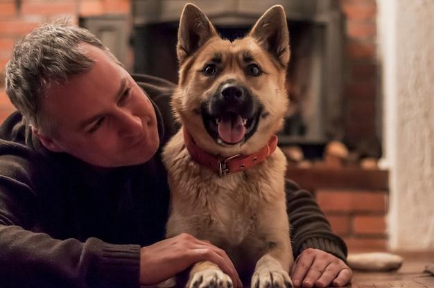 Bel homme avec un chien mignon à la maison. Attractive