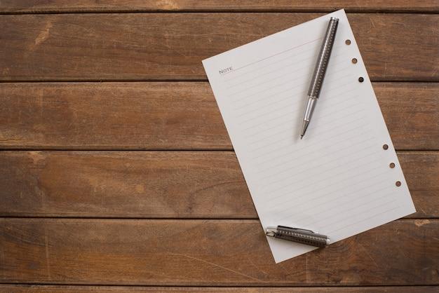 Bloc-notes avec un stylo sur la table en bois de bureau. Photo gratuit