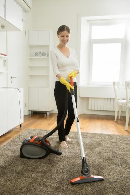 bonne femme souriante nettoyant le tapis t l charger des photos gratuitement. Black Bedroom Furniture Sets. Home Design Ideas
