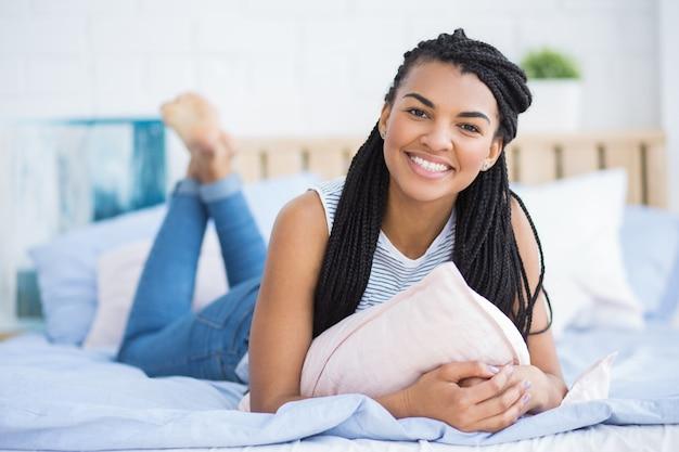 bonne jeune femme afro am ricaine reposant au lit t l charger des photos gratuitement. Black Bedroom Furniture Sets. Home Design Ideas