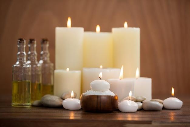 bougies avec des bouteilles d 39 huile de massage et de sel de mer dans un bol en bois. Black Bedroom Furniture Sets. Home Design Ideas