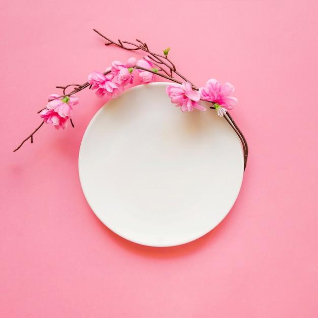 Brindille fleurie près de la plaque Photo gratuit