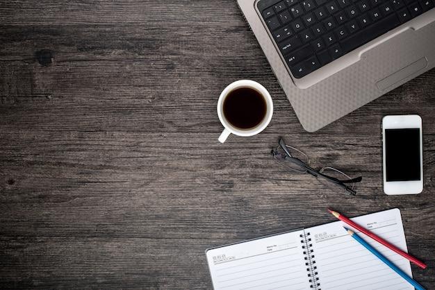 Bureau avec un ordinateur portable, une tasse de café et un calendrier Photo gratuit