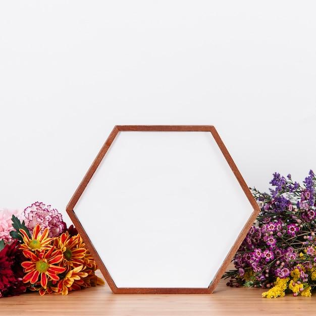 Cadre en forme d'image parmi les fleurs Photo gratuit