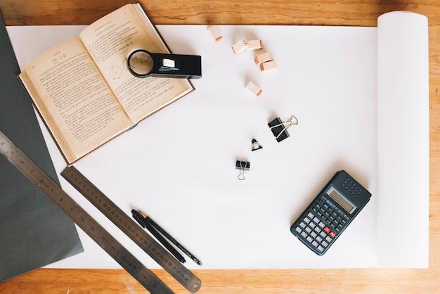 Calculatrice et livre sur papier déroulé Photo gratuit