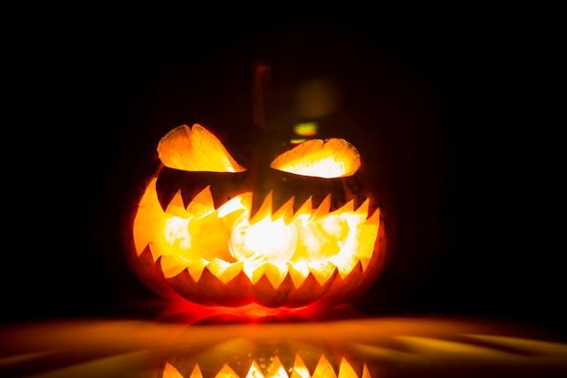 citrouille d 39 halloween avec la bouche ouverte et la lumi re l 39 int rieur et sur un fond noir. Black Bedroom Furniture Sets. Home Design Ideas