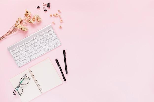 Clavier; fleurs blanches; trombones bulldog; stylo et lunettes sur cahier sur fond rose Photo gratuit
